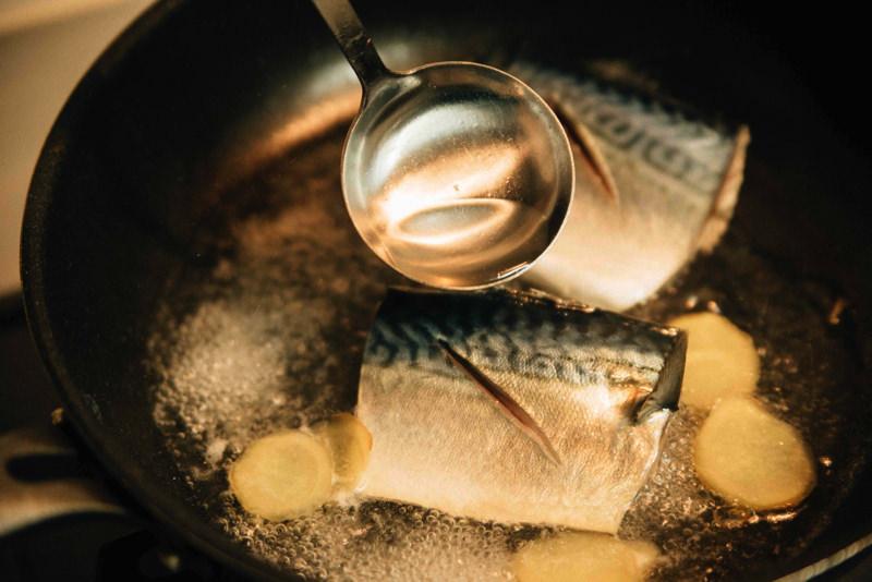 さばとスライスした生姜を加え、煮汁をさばの表面に回しかける