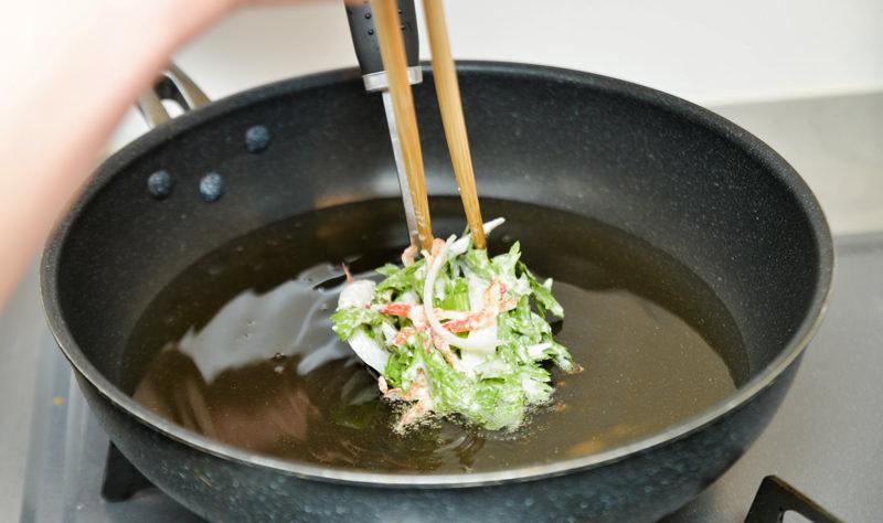 生地の1/4をお玉ですくって、箸などで押しだしながらゆっくりと流し入れる