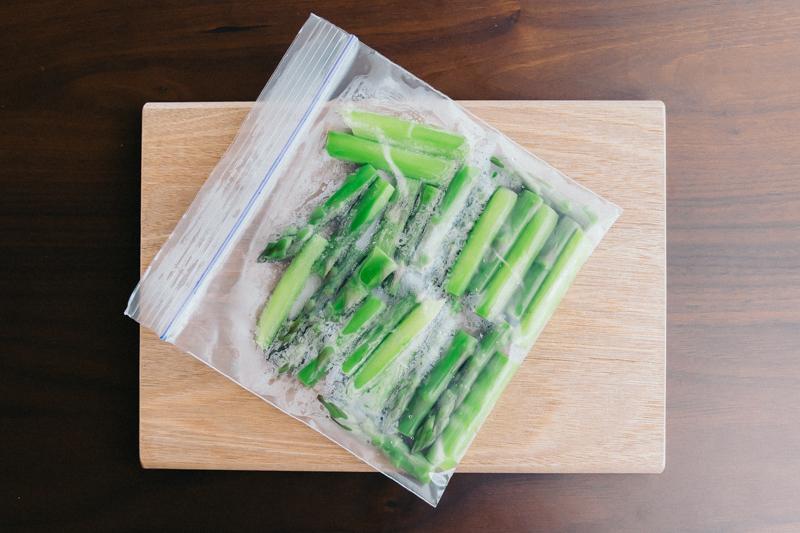 茹でて粗熱をとったアスパラを、チャック付き保存袋に入れて冷凍する。