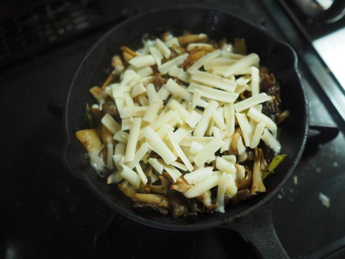 フライパンで炒めた具材のうえにチーズをのせる