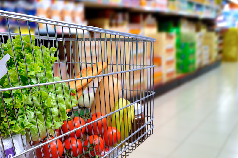 Shopping cart full of food in supermarket aisle side tilt