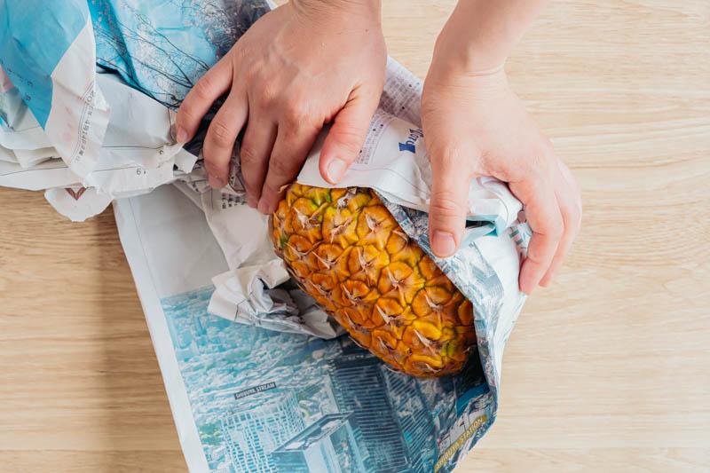 パイナップルを新聞紙に包む