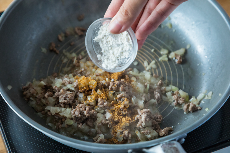炒めた合いびき肉に薄力粉を加える